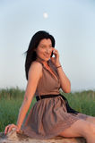 Young Woman In Meadow Talking on Mobile Phone Royalty Free Stock Photo