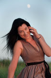 Young Woman In Meadow Talking on Mobile Phone Royalty Free Stock Image