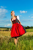 Young woman on meadow wearing dirndl Stock Photography