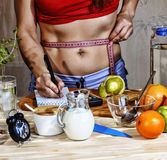 Young woman measures. Detox. Young girl measures the waist and uses proper nutrition. Detox drinks, ingredients, dumbbells. Concep Stock Photography