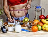 Young woman measures. Detox. Young girl measures the waist and uses proper nutrition. Detox drinks, ingredients, dumbbells. Concep Stock Image