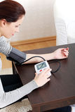 Young woman measurind her blood pressure at home. Stock Images