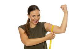 Woman measuring her biceps. Young woman measuring her biceps with a measuring tape on a white background stock image