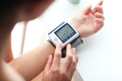 High blood pressure. Young woman measuring her blood pressure Royalty Free Stock Photo