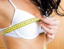 Young woman measuring her breast at home Stock Photo