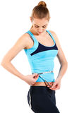 Young woman measuring her stomach with measuring tape Royalty Free Stock Image