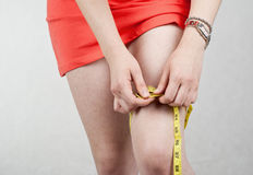 Young woman measuring her thigh stock photo