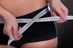 Young Woman Measuring Her Waist Royalty Free Stock Photos