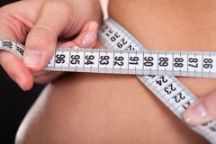 Young woman measuring her waist Stock Photography