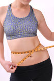 Young woman measuring her waistline Royalty Free Stock Photos