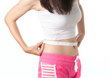 Young woman measuring her waistline with measuring tape Stock Photo