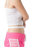 Young woman measuring her waistline with measuring tape Royalty Free Stock Image