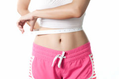 Young woman measuring her waistline with measuring tape Royalty Free Stock Photo