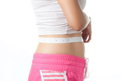 Young woman measuring her waistline with measuring tape Stock Image