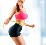 Young woman measuring herself. Weight loss Royalty Free Stock Photo