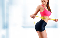 Young woman measuring herself. Weight loss Stock Photo