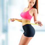 Young woman measuring herself. Weight loss Royalty Free Stock Photos