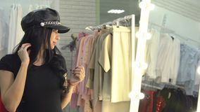 Young woman is measuring on a leather hat on a mirror in a clothing store.  stock video