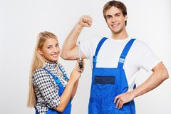 Young woman measuring repairman biceps Royalty Free Stock Images