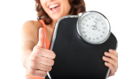 Young woman with measuring scale. Diet and weight - young woman with a scale, she is happy about the success Stock Photos