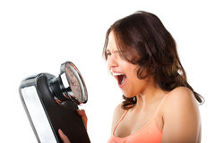 Young woman with measuring scale. Diet and weight, young woman with a scale, she is desperate and shouting Royalty Free Stock Image