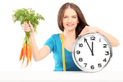 Young woman with measuring tape holding carrots and a wall clock Royalty Free Stock Image