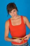Young woman measuring waist. Half body portrait of young woman with tape measure around waist, blue background Stock Photo