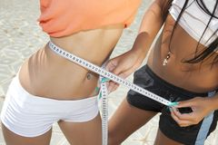 Young woman measuring waist of her girl friend Stock Photos