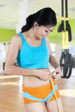 Young woman measuring waistline at gym Royalty Free Stock Photos