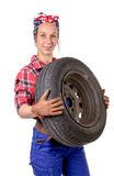 Young woman mechanic with a car wheel Royalty Free Stock Photo