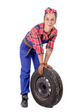 Young woman mechanic with a car wheel Stock Image