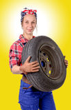 Young woman mechanic with a car wheel Stock Photo