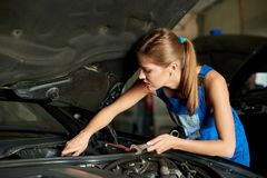 Young woman mechanics repairing or inspecting a car stock photo