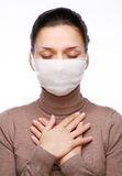 Young woman in medical mask. Keeping hands on chest Stock Images