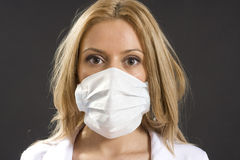 Young woman with medical mask. Young woman wearing medical mask to protect from influenza virus Royalty Free Stock Photo