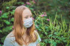 Young woman in a medical mask because of an allergy to ragweed.  Royalty Free Stock Photo