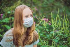 Young woman in a medical mask because of an allergy to ragweed.  Stock Photography