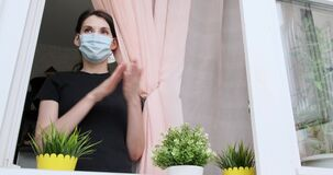 Young woman in medical mask applauds in window in support of people who fight against coronavirus. Girl applause from