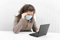 The young woman in medical mask with the laptop. The young woman with medical mask keeps for sick head and works with the laptop Stock Photography