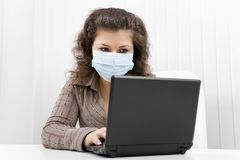 The young woman in medical mask with the laptop. The young woman at office in medical mask works with the laptop Stock Photo
