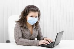 The young woman in medical mask with the laptop Royalty Free Stock Photography