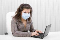 The young woman in medical mask with the laptop. The young woman at office in medical mask works with the laptop Royalty Free Stock Image