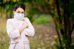 Young woman in a medical mask wrapped herself in a light coat on a cool autumn day. Copy space