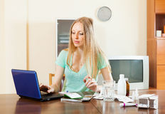 Young woman with medications and laptop Royalty Free Stock Photo