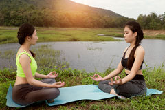 Young woman meditates while practicing yoga outdoor in park,  re Stock Photos