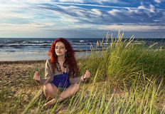 Young woman meditates on seacoast Stock Images