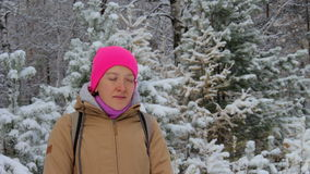 Young woman meditates in a snowy winter forest during snowfall. Young woman in a bright pink hat meditates in a snowy winter forest during snowfall. Snowflake stock video footage