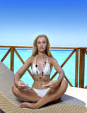 The young woman meditates on a sundeck of house over sea water, Maldives Royalty Free Stock Photography
