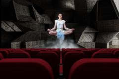 Young woman meditating in air in 3d room with empty cinema  seats Stock Image