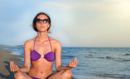 Young woman meditating alone at the beach Stock Images